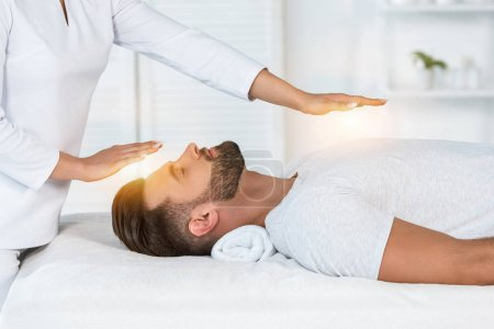 Photo for Cropped view of healer putting hands above head while healing handsome man on massage table - Royalty Free Image