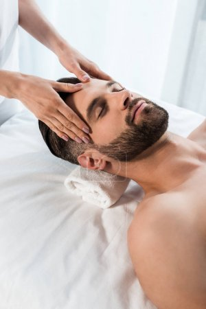 Photo pour Cropped view of masseur doing massage to handsome man with closed eyes - image libre de droit