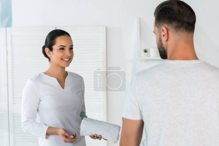 cheerful woman looking at bearded man while holding towel in spa center