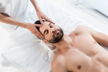 Photo for Overhead view of masseur doing massage to handsome man with closed eyes - Royalty Free Image