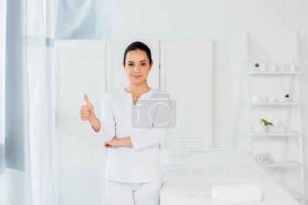 Photo pour Attrayant masseur debout dans le centre de spa et montrant pouce vers le haut - image libre de droit