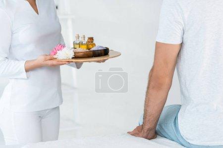 Photo pour Vue recadrée du plateau de fixation de masseur avec des bouteilles d'huile, des cuvettes avec le sel de mer et des fleurs près de l'homme dans le centre de spa - image libre de droit