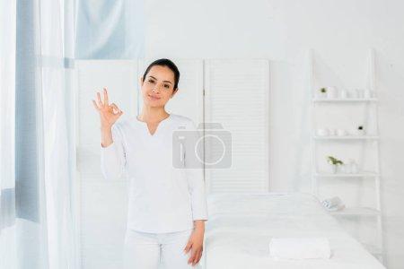 Photo pour Femme gaie de brunette affichant le signe ok dans le centre de spa - image libre de droit