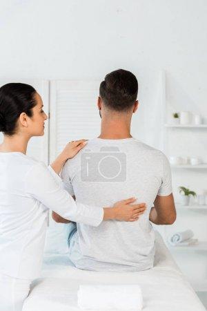 Photo pour Vue arrière de l'homme s'asseyant sur la table de massage près du guérisseur attrayant - image libre de droit