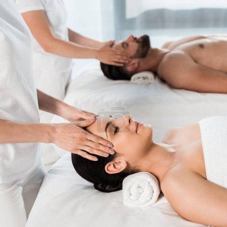 Photo pour Vue recadrée des masseurs faisant le massage à la femme et à l'homme dans le centre de spa - image libre de droit