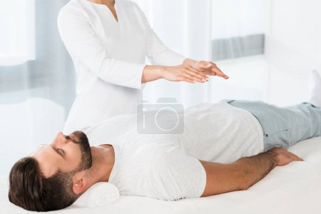 Photo for Cropped view of woman putting hands above body while healing handsome man - Royalty Free Image