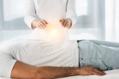 cropped view of woman putting hands above body while healing man