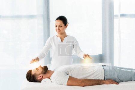 Photo pour Attrayant femme mettre les mains au-dessus du corps tout en guérissant bel homme barbu - image libre de droit