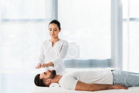 Photo pour Attrayant guérisseur mettre les mains au-dessus de la tête tout en guérissant bel homme barbu - image libre de droit