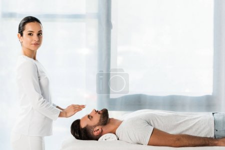 Photo for Beautiful healer putting hands above head of man with closed eyes - Royalty Free Image
