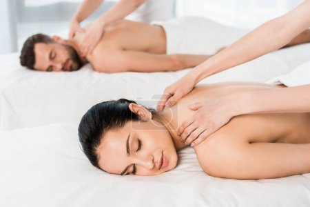 Photo for Selective focus of masseur doing massage to woman with closed eyes near man in spa center - Royalty Free Image