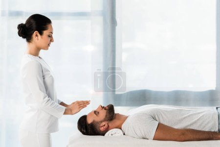 Photo for Attractive brunette healer putting hands above head of bearded man with closed eyes - Royalty Free Image