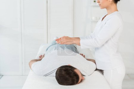 Photo for Cropped view of healer putting hands above back of man on massage table - Royalty Free Image