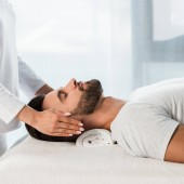 cropped view of woman healing bearded man with closed eyes