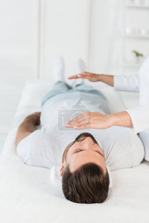 Photo for Cropped view of healer with hands above body of bearded man with closed eyes - Royalty Free Image