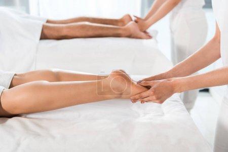 Photo pour Foyer sélectif du masseur faisant le massage de jambe à la femme près de l'homme - image libre de droit