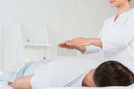 Photo for Low angle view of healer with hands above body of man - Royalty Free Image