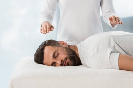 Photo for Cropped view of healer with hands above body of man on massage table - Royalty Free Image