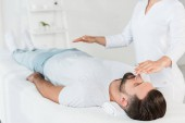 cropped view of healer with hands above body of man resting on massage table