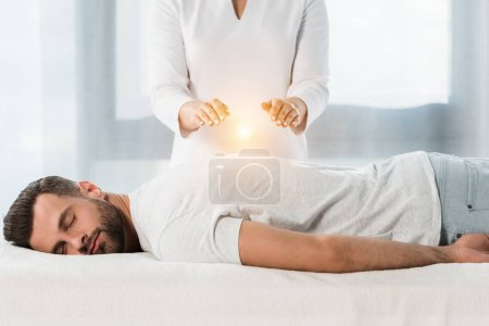 Photo for Cropped view of woman healing man while putting hands above body - Royalty Free Image