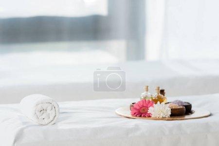 Photo pour Foyer sélectif du plateau avec des bouteilles d'huile, des cuvettes avec le sel de mer et des fleurs dans le centre de spa - image libre de droit