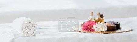 Photo pour Coup panoramique du plateau avec des bouteilles d'huile, des cuvettes avec le sel de mer et des fleurs dans le centre de spa - image libre de droit