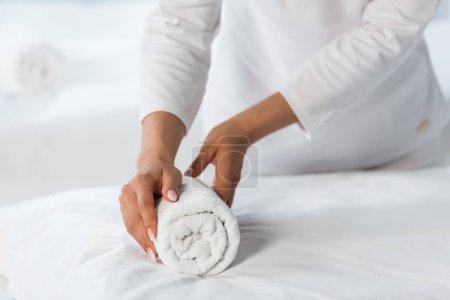 Photo pour Vue recadrée du masseur debout près de la table de massage et tenant rouleau de serviette - image libre de droit