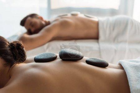 enfoque selectivo de la mujer que tiene masaje de piedra cerca del hombre en el centro de spa