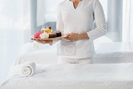 Photo pour Vue recadrée du plateau de fixation de masseur avec des bouteilles d'huile, des cuvettes avec le sel de mer et des fleurs dans le centre de spa - image libre de droit