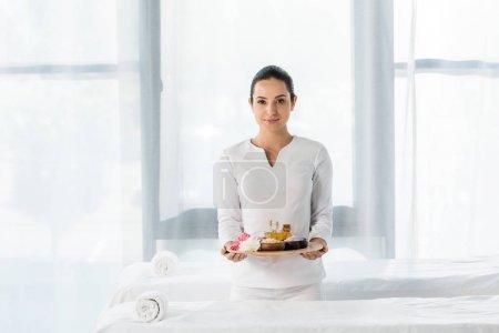 Photo pour Attrayant masseur brunette tenant plateau avec des bouteilles d'huile, bols avec du sel de mer et des fleurs dans le centre de spa - image libre de droit