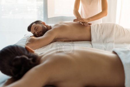 Photo for Selective focus of masseur doing massage to man near brunette woman in spa center - Royalty Free Image