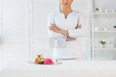Photo pour Vue recadrée du masseur debout avec bras croisés près du plateau avec bouteilles d'huile, sel de mer et fleurs - image libre de droit