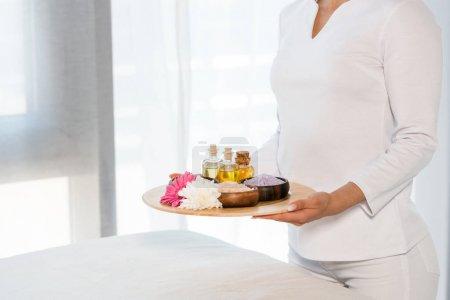 Photo pour Vue recadrée du plateau de fixation de femme avec des bouteilles d'huile, de sel de mer et de fleurs - image libre de droit