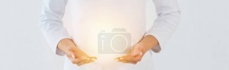 Photo pour Panoramic shot of healer standing and gesturing near light isolated on white - image libre de droit