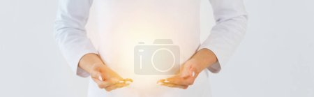 Foto de Foto panorámica de sanador de pie y gesturing cerca de la luz aislada en blanco - Imagen libre de derechos
