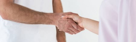 Photo pour Panoramic shot of man and woman shaking hands isolated on white - image libre de droit