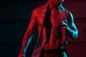 "Постер, картина, фотообои ""cropped view of shirtless fireman holding fire hose in darkness"""
