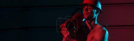Foto de Disparo panorámico de bombero sexy sosteniendo extintor en la oscuridad - Imagen libre de derechos