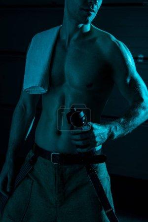 Photo pour Vue partielle de sexy homme torse nu avec serviette tenant bouteille de sport dans l'obscurité - image libre de droit