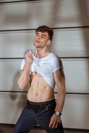 Photo pour Homme musclé sexy en t-shirt blanc montrant torse - image libre de droit