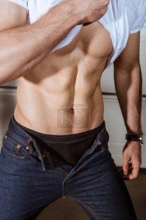 Photo pour Vue recadrée de l'homme musclé sexy en t-shirt blanc montrant torse - image libre de droit