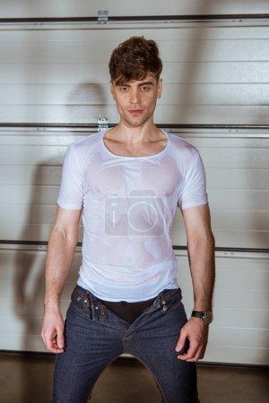Photo pour Bel homme en jeans et t-shirt blanc mouillé - image libre de droit