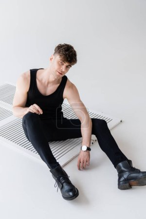 Photo for Man in black sleeveless shirt sitting on grey - Royalty Free Image