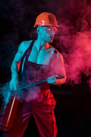 Foto de Sexy bombero sin camisa en general sosteniendo extintor de incendios en humo en negro - Imagen libre de derechos
