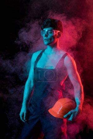 Photo pour Pompier torse nu sexy dans l'ensemble tenant hardhat dans la fumée sur le noir - image libre de droit