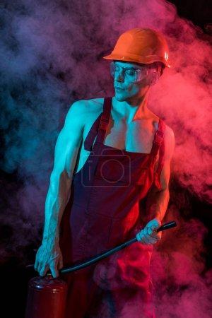 Foto de Sexy sin camisa bombero en general la celebración de extintor de incendios en el humo en negro - Imagen libre de derechos
