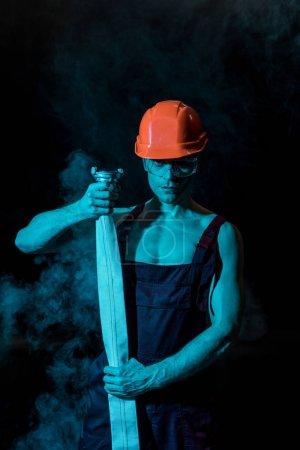Foto de Bombero sexy en hardhat y gafas protectoras que sostienen la manguera de fuego en humo en negro - Imagen libre de derechos