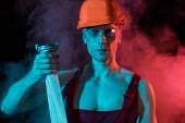 "Постер, картина, фотообои ""sexy fireman in hardhat and protective goggles holding fire hose in smoke on black"""
