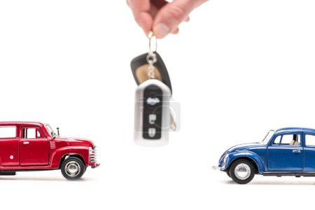Photo for Cropped view of man holding key near toy cars on white - Royalty Free Image