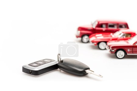 Photo for Keys and red toy cars on white surface - Royalty Free Image